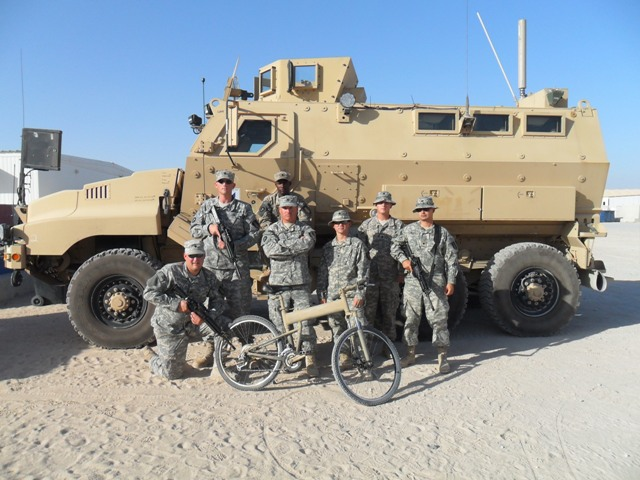 Paratrooper folding bike and soldiers in front of vehicle