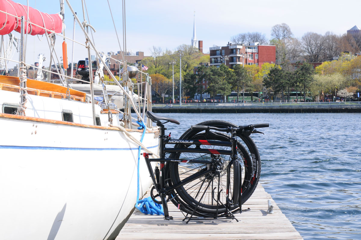 Montague Allston folding bike on dock by sailboat